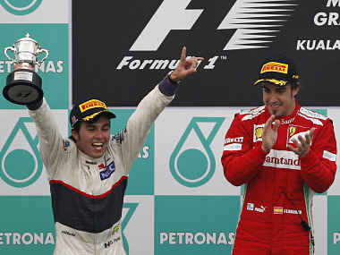 Sauber Formula One driver Sergio Perez celebrates his second position next to Ferrari's Alonso during the podium ceremony following the Malaysian F1 Grand Prix at Sepang International Circuit. Reuters