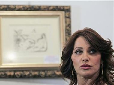 Former Romanian Olympic gold medal gymnast Comaneci looks on before a charity auction in Bucharest. Reuters