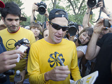 Lance Armstrong signs autographs following a run with his fans at Mount Royal park in Montreal. Reuters
