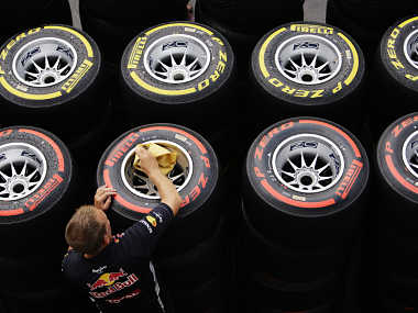 A Red Bull Formula One crew member wipes rain water off Pirelli tyres in the paddock ahead of the first practice session of the Singapore F1 Grand Prix. Reuters
