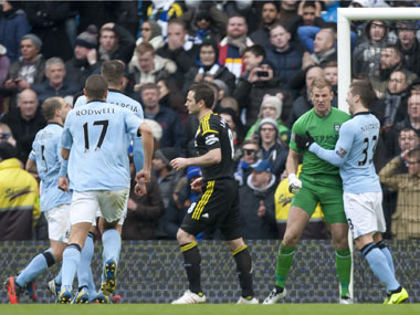 Manchester City's goalkeeper Joe Hart, center right, celebrates with teammates after saving a penalty from Chelsea's Frank Lampard during their English Premier League soccer match at The Etihad Stadium, Manchester on Sunday. AP
