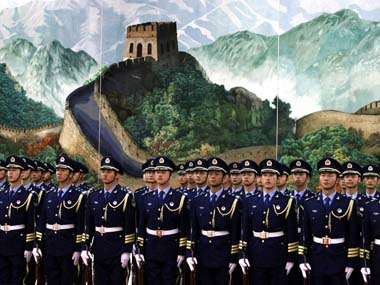A Chinese honour guard stand in front of a painting depicting the Great Wall. Reuters