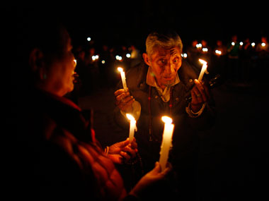 An elderly exile Tibetan participates in a candle-lit vigil in solidarity with fellow Tibetans who have self immolated, in Kathmandu. Associated Press