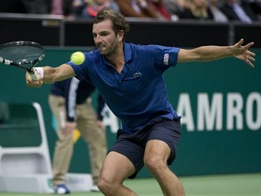 Julien Benneteau returns a shot against Roger Federer . AP