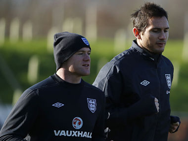 England's Rooney jogs with Lampard during a training session at the St George's Park training complex near Burton Upon Trent. Reuters