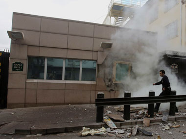An embassy security guard arrives at the Gate 2 of the US embassy just minutes after a suicide bomber has detonated an explosive device at the entrance of the U.S. Embassy in the Turkish capital, Ankara. AP