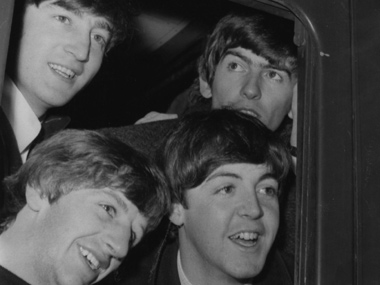 The Beatles looking out of a train window. Getty Images