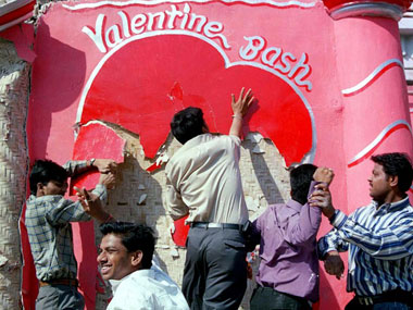 Shiv Sena party workers destroy a Valentine's Day hoarding in Mumbai. AFP