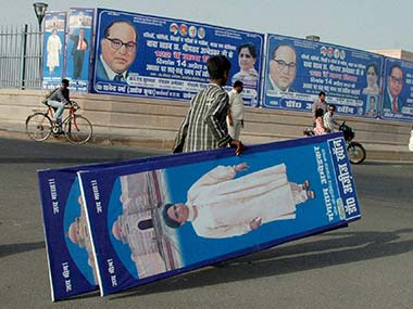 Administration officials remove the hoardings put up by BSP workers in Lucknow on the eve of Ambedkar Jayanti on Saturday. PTI