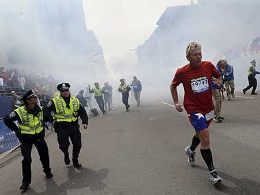 A Boston Marathon competitor and Boston police run from the area of an explosion near the finish line in Boston. AP