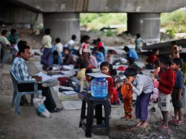 A boy drinks water, as others wait at a free school run under a mass transit bridge: AP