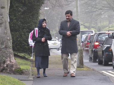 Malala Yousufzai walks with her father Ziauddin as she attends Edgbaston High School for girls in Edgbaston. Reuters