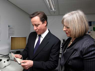 File photo of Britain's PM David Cameron and Home Secretary Theresa May looking at passports during a visit to UK Border Agency staff. Reuters