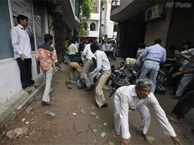 Bystanders duck for cover during a police-terrorist encounter at Batla House in Jamia Nagar, Delhi. IBNLive
