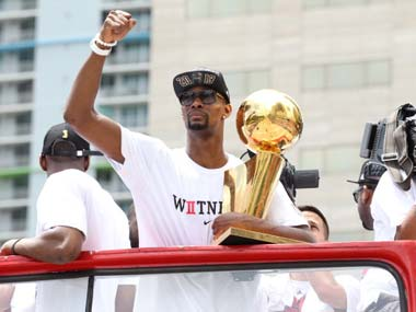 Chris Bosh cradles the NBA championship trophy during the Miami Heat's victory parade. Getty