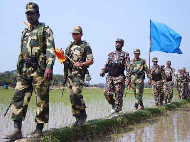 Border Security Force (L, with orange flag) and Bangladesh Rifles troopers (R, with blue flag) conduct a joint foot patrol on the zero line, the India-Bangladesh border, in Nischintapur. AFP