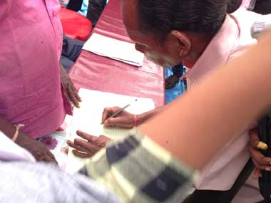 Village head signs the palli sabha resolution after 3.5 hours of high drama. Image courtesy: Jay Mazoomdar