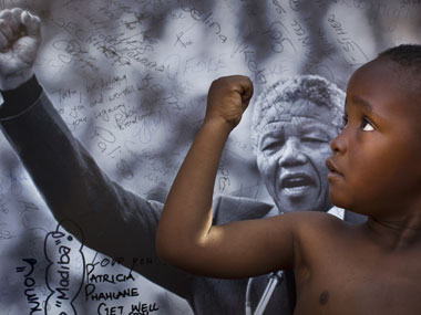 A young member of the Maitibolo Cultural Troupe, who came to dance for well-wishers in honor of Nelson Mandela, poses for well-wishers in front of a placard of Mandela. AP