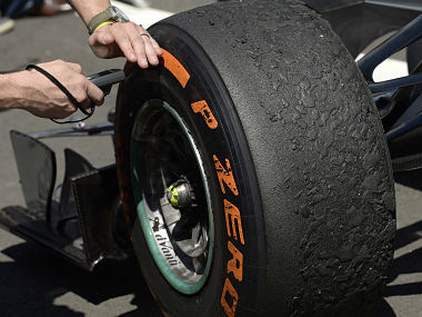 The tyres on Mercedes Formula One driver Rosberg of Germany's car are checked by an official after the British Grand Prix. Reuters