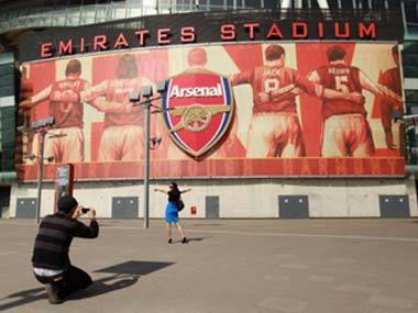 Fans take a picture in front of the Emirates Stadium. Getty Images