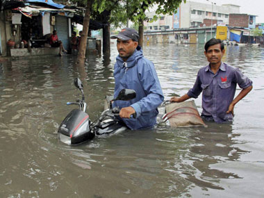 Commuters wade through flood water after heavy rains in Ahmedabad on Saturday. PTI