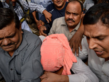 The juvenile in the Delhi gangrape case being escorted to court. AFP