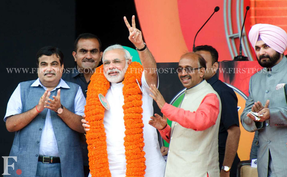 Modi getting garlanded by the Delhi unit of BJP before his speech. BJP leader Nitin Gadkari  (L) and Vijay Goel  (R) are also seen.  Naresh Sharma/Firstpost.