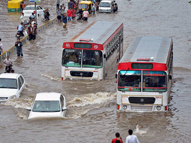 Vehicles move through a flodded road after heavy rains in Ahmedabad on Wednesday. PTI