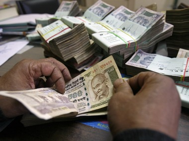 An employee counts Indian rupee notes at a cash counter inside a bank in Agartala. Reuters