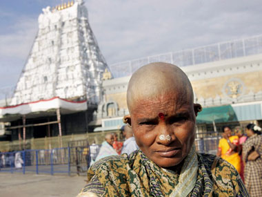 A devotee poses before the Tirupati temple. AFP