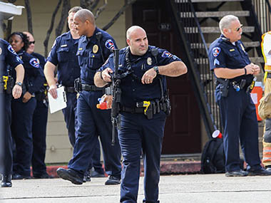 Policeman carrying weapon walks in front of the Silverwood Apartments where a suspect barricaded himself after a shooting and a gunfight with police in Arlington. Reuters