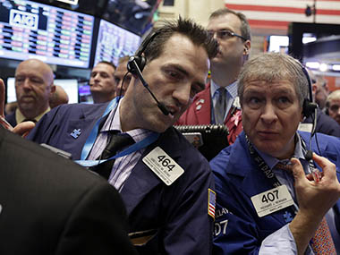 FILE - In this Wednesday, Nov. 13, 2013, file photo, traders Gregory Rowe, left, and Richard Newman confer on the floor of the New York Stock Exchange. World stock markets bounced higher Thursday Nov. 14, 2013 after prepared testimony for the confirmation hearing of incoming Federal Reserve chief suggested the U.S. central bank won't reduce its economic stimulus until March next year or later.AP