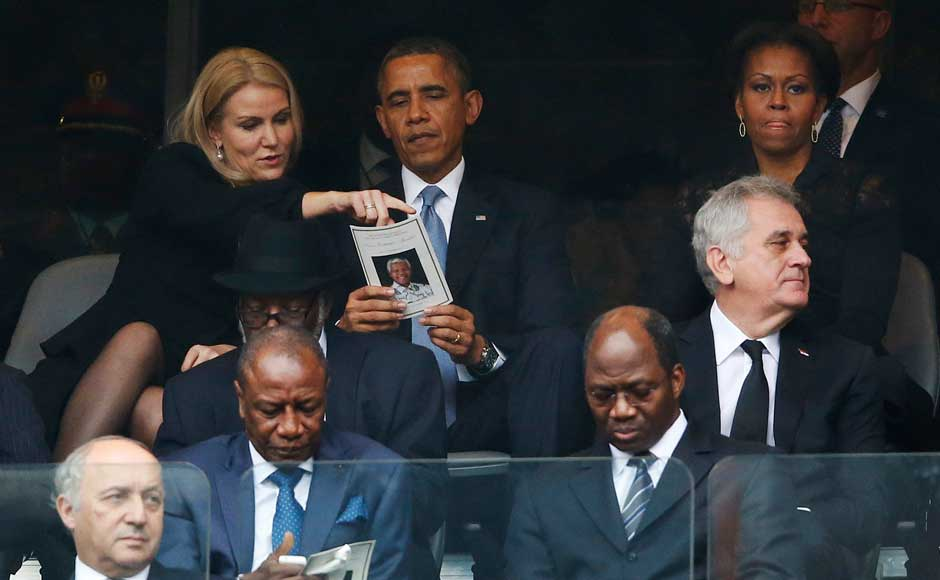 President Barack Obama talks with Danish prime minister, Helle Thorning-Schmidt, left, as first lady Michelle Obama looks on at right during the memorial service for former South African president Nelson Mandela at the FNB Stadium in Soweto, near Johannesburg, South Africa, Tuesday Dec. 10, 2013. AP