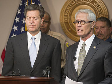 Kansas Gov. Sam Brownback, left, listens as U.S. Attorney Barry Grissom announces the arrest of Terry Lee Loewen, 58, of Wichita, Kan., during a news conference on Friday, Dec. 13, 2013, in Witchita, Kan. Grissom said Loewen was arrested Friday morning at Mid-Continent regional airport where he planned to drive a car that he believed was full of explosives into a terminal at the airport. AP