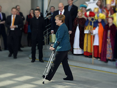 German Chancellor Angela Merkel walks with crutches upon arrival at the Chancellery in Berlin. AFP