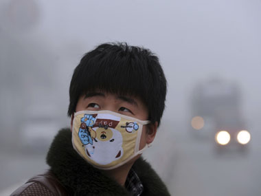 A Chinese man wearing a face mask: Reuters
