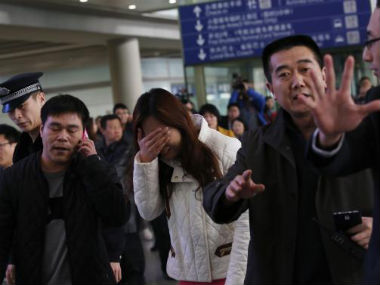 A woman believed to be the relative of a passenger onboard Malaysia Airlines flight MH370, covers her face as she cries at the Beijing Capital International Airport in Beijing. Reuters