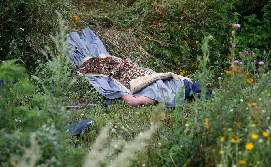 Print :Photos: Ukraine rebels move MH17 victim's bodies, tamper with