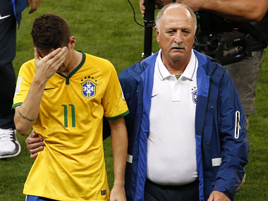 Brazil's Oscar (L) is comforted by coach Luiz Felipe Scolari after they lost their 2014 World Cup semi-finals against Germany. Reuters