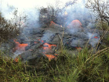 In this photo provided by the U.S. Geological Survey, the active lava flow front continues to advance downslope towards the northeast about a mile and a half from the marketplace in Pahoa, Hawaii. AP