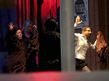 Hostages run towards armed tactical responce police as they run to freedom from a cafe under siege at Martin Place. PTI
