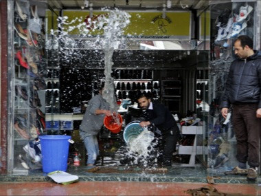 Kashmiri shopkeepers try to remove water from inside a footwear shop following heavy rains in Srinagar, Indian controlled Kashmir. AP