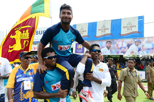 Kumar Sangakkara (C) gestures to the crowd as his teammates Dhammika Prasad (L) and Vishwa Fernando (R) carry him around the pitch in a lap of honour after the 2nd Test. AFP