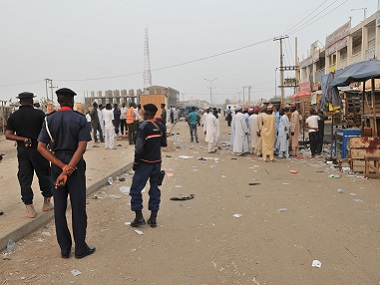 Security officers stand guard at the scene of an  explosion at a mobile phone market in Kano, Nigeria. (AP Photo)
