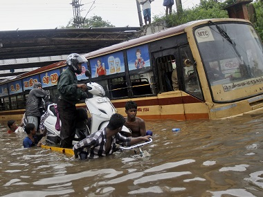 People help a man carry his two-wheeler on a cycle cart as they wade through a waterlogged subway in Chennai. AP