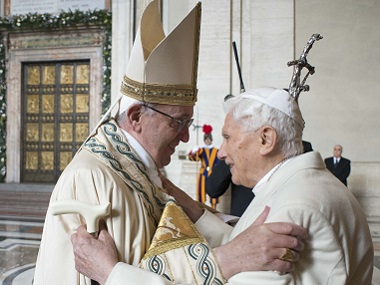 "Pope Francis (L) welcomes Pope emeritus Benedict XVI before the opening of the ""Holy Door"". File photo AFP / Osservatore Romano"