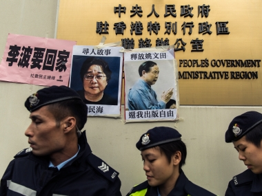 Police walk past missing person notices of Gui Minhai  and Yau Wentian. AFP