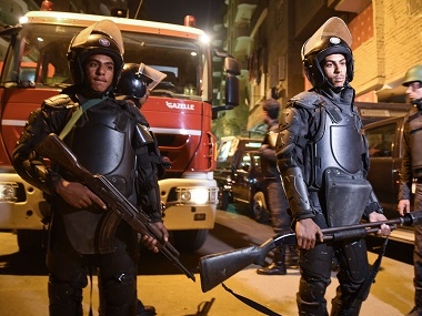 Security personnel stand guard at the scene of the bomb blast in a main street in Giza. AFP