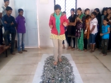 A student walks on broken glass as her classmates wait in line. Screengrab from YouTube