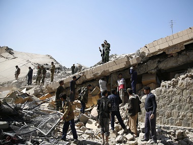 Policemen and civilians search for victims at the site of a Saudi-led airstrike on the police headquarters in Sanaa, Yemen. AP